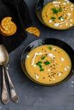 Soupe crème végétale avec le basilic, le sésame noir et les biscuits de fromage Photographie stock
