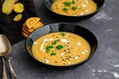 Soupe crème végétale avec le basilic, le sésame noir et les biscuits de fromage Images stock
