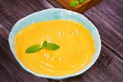 Soupe crémeuse à courge de potiron ou de butternut dans une cuvette, potiron rôti entier sur le fond en bois Photos stock