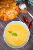 Soupe crémeuse à courge de potiron ou de butternut dans une cuvette, potiron rôti entier sur le fond en bois Photo stock