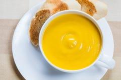 Soupe crémeuse à potiron avec la baguette légèrement grillée images stock