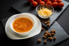 Soupe crémeuse à tomate avec du fromage sur le fond en bois noir Pains grillés de pain, des tomates-cerises, des épices et de l'a Photos libres de droits
