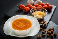 Soupe crémeuse à tomate avec du fromage sur le fond en bois noir Pains grillés de pain, des tomates-cerises, des épices et de l'a Image stock
