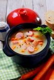 Soupe crémeuse saine savoureuse avec la saucisse sur le pot Image stock