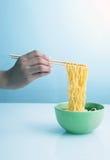 Soupe de nouilles avec des baguettes de fixation de main Photographie stock libre de droits