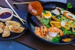 Soupe de nouilles avec des fruits de mer comprenant des moules, des crevettes roses, des calmars, des oeufs et des légumes photographie stock libre de droits