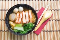 Soupe de nouilles d'oeufs avec le rôti de porc rouge sur le fond en bois Image stock