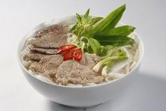 Soupe de nouilles de riz avec du boeuf rare coupé en tranches (Vietnam Pho) Photographie stock libre de droits