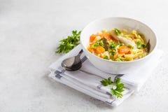 Soupe de nouilles et légumes de poulet dans une cuvette blanche sur un Ba blanc photographie stock libre de droits
