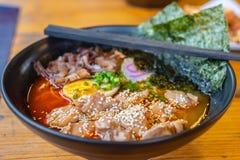 Soupe de nouilles japonaise de ramen épicés dans un bol noir de ramen de couleur photographie stock