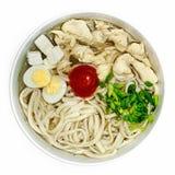 Soupe de nouilles, poulet, oeuf et oignon vert dans un plat sur un fond blanc Photos stock