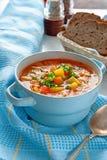 Soupe de poulet et de légumes avec des champignons et des tomates dans une soupière bleue avec des poignées sur une table avec le Photo libre de droits