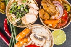 Soupe des nouilles avec des crevettes, des fruits de mer, le poulet et des légumes a images stock