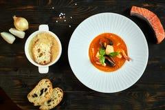 Soupe faite maison à fruits de mer avec la sauce tomate et le lait de noix de coco sur un vieux plateau en bois Photos libres de droits
