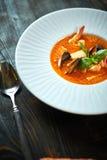 Soupe faite maison à fruits de mer avec la sauce tomate et le lait de noix de coco sur un vieux plateau en bois Images libres de droits