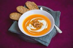 Soupe faite maison à patate douce et à carotte avec les piments et le gingembre décorés par la crème sure et l'arachide rôtie dan Photo libre de droits