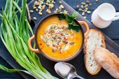 Soupe faite maison à potiron avec de la crème, le pain, des verts et des graines de citrouille sur un fond en bois Viev supérieur Photos stock