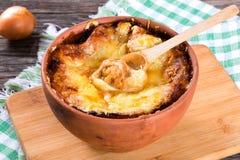Soupe française à gratin d'oignon dans un pot d'argile, recette authentique, cuillère en bois sur une planche à découper sur une  images stock
