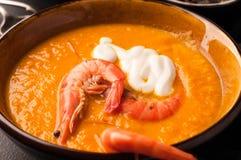 Soupe orange à potiron avec la crevette et acidifier dans la cuvette foncée photographie stock