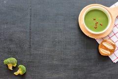 Soupe, pain et brocoli verts à purée sur une table noire Image stock