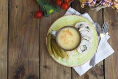 Soupe-purée dans une cuvette et un rouleau de filet de poulet d'un plat de vert fond et tomates-cerises en bois photos libres de droits