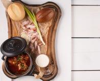 Soupe rouge à borsch dans une petite casserole placée sur les conseils blancs Vue de ci-avant Photos stock