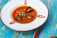 Soupe rouge avec des huîtres dans un plat blanc photographie stock libre de droits