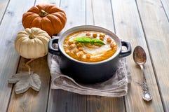 Soupe savoureuse à potiron dans la casserole en céramique noire sur le bois rustique Photo stock