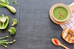 Soupe verte à purée, pain et légumes verts sur une table noire Photos libres de droits