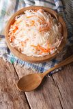 Sour cabbage and carrots in a wooden plate. vertical top view Stock Images