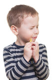Sour candy. Cute boy eating sour candy on isolated white Royalty Free Stock Images
