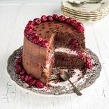 Sour cherry chocolate cake. On a white wooden table board royalty free stock photo