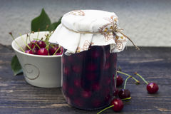 Sour cherry compote. Jar with sour cherry compote on the wooden table royalty free stock image