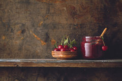 Sour Cherry Jam. Jar of cherry jam, sour cherries and spoon Royalty Free Stock Photos