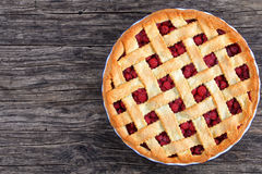 Sour cherry pie with pretty lattice top. Delicious homemade sour cherry pie with pretty lattice top and golden crust in baking dish on old dark wooden table royalty free stock photo