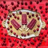Sour cherry popsicles. Homemade sour cherry popsicles on a vintage plate royalty free stock photography