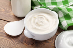 Sour cream in a bowl and milk bottle. On wooden table royalty free stock photography