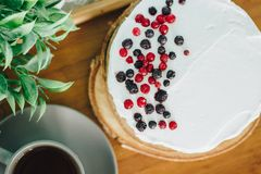 Sour cream cake, topped with berries with a hot cup of coffee Stock Photos