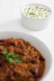 Sour cream and chives with a chilli. Sour cream and chives on a white tablecloth with chilli con carne in the foreground Royalty Free Stock Photo