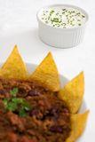 Sour cream & chives with chilli-con-carne. A ramekin filled with sour cream and chives on a white tablecloth, with a dish of chilli con carne with tortilla chips Stock Photos