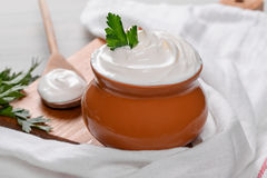 Sour cream in a clay pot. Shot closeup royalty free stock image