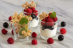 Sour cream in a glass with raspberries and currants. Assorted berries with sour product. Sour cream in a glass with raspberries and currants. Assorted berries Stock Image