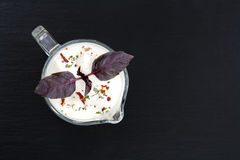Sour cream in sauce boat with basil and spices Stock Photography
