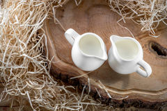 Sour cream in the white jugs on wooden desk with hay, up view Royalty Free Stock Photos