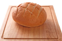 Sour Dough Bread isolated. A loaf of sourdough bread on a wooden cutting board isolated against white, with clipping path Stock Photos