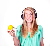 Sour music. Girl listening to sour music from a lemon royalty free stock photography