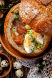The sour soup Żurek made of rye flour with smoked sausage and eggs served in bread bowl. royalty free stock photography