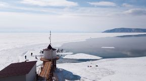 The source of the Angara river from lake Baikal. Spring in Siberia-a group of people walking on ice. Beautiful lighthouse. By the shore royalty free stock photography