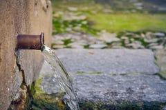 Source d'eau naturelle avec une conduite d'eau simple photo libre de droits