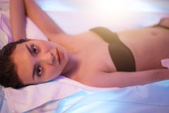 A source of energy. good-looking girl with black hair lying on the tanning bed. A source of energy. good-looking girl with black hair lying on the modern tanning stock photography